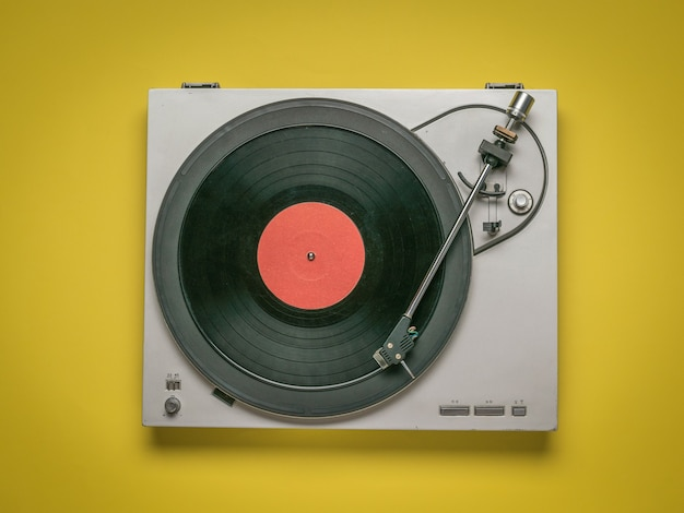 Vintage vinyl record player on yellow wall. retro equipment for playing music.