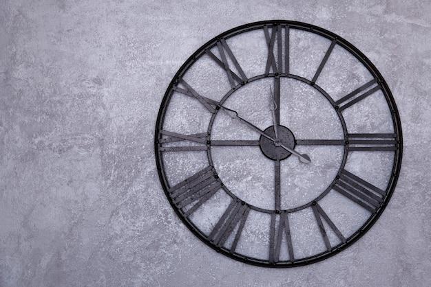 벽에 로마 숫자와 함께 빈티지 벽 시계. 회색 치장 벽토 벽. 시계는 10-12 11을 보여줍니다