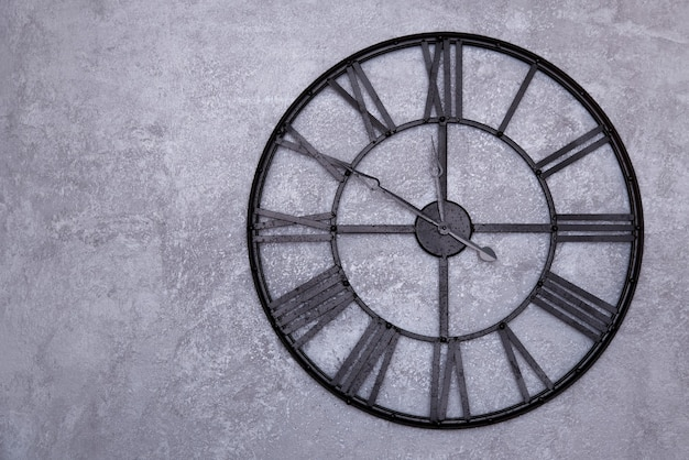 Vintage wall clock with roman numerals on the wall. gray stucco wall. clock shows ten to twelve 11