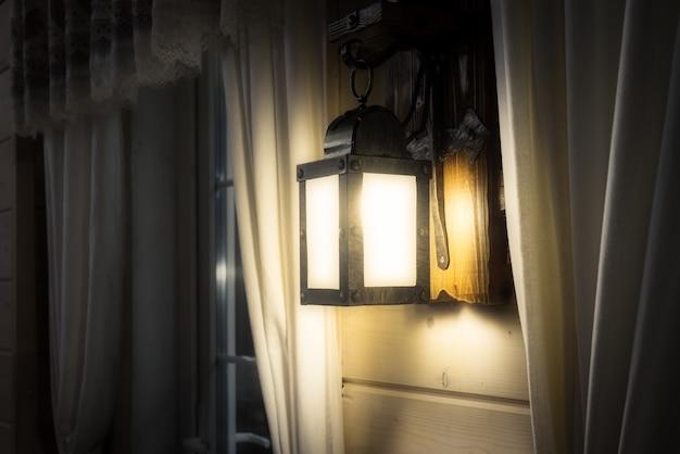 暗い木造家屋のインテリアデザインで飾られた電球に輝くヴィンテージの壁ランプ