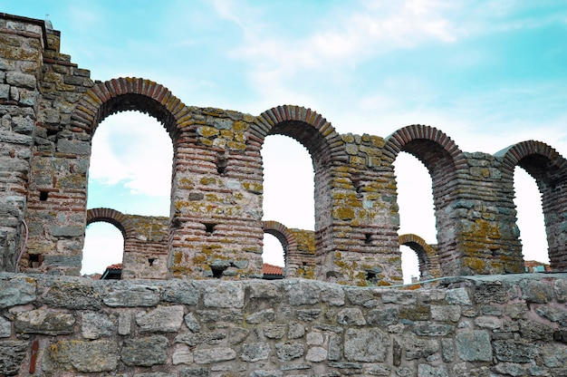Vintage wall of stone with arches with blue sky