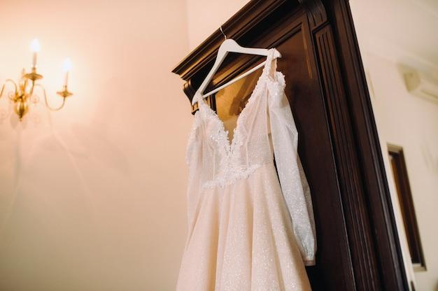 Vintage wedding dress hanging on a wooden hanger.