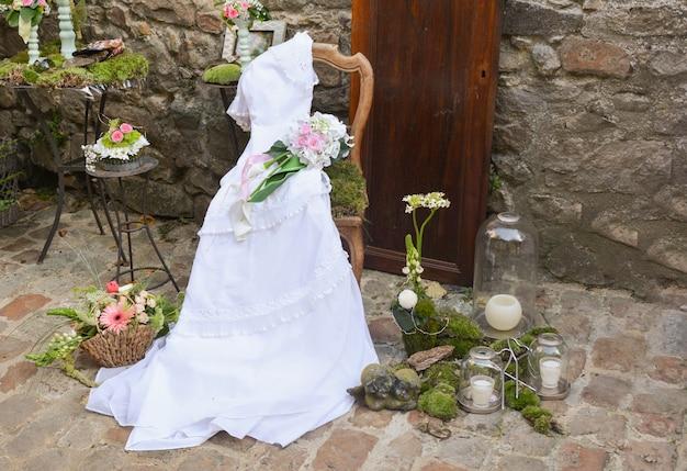 石の壁を背景に木製の椅子にヴィンテージのウェディングドレス