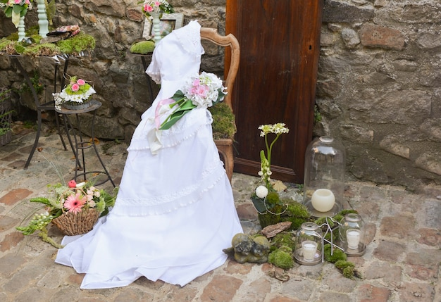 Vintage wedding dress on a wooden chair against the backdrop of a stone wall