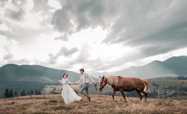 ピークの丘の上の馬と牧場で新郎新婦のビンテージのウェディング