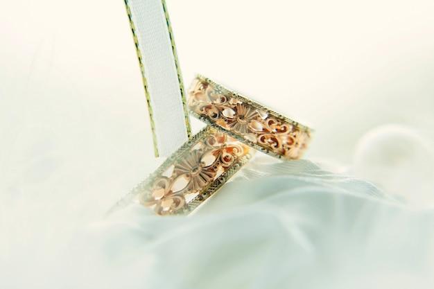 白いリボンの中でビンテージの結婚指輪、クローズアップ。白い背景をぼかした写真のパターンを持つ金の指輪。結婚式と家族の伝統。