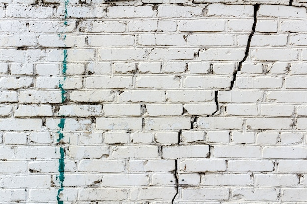 Vintage white brick wall with a deep crack and spots of paint. abstract background