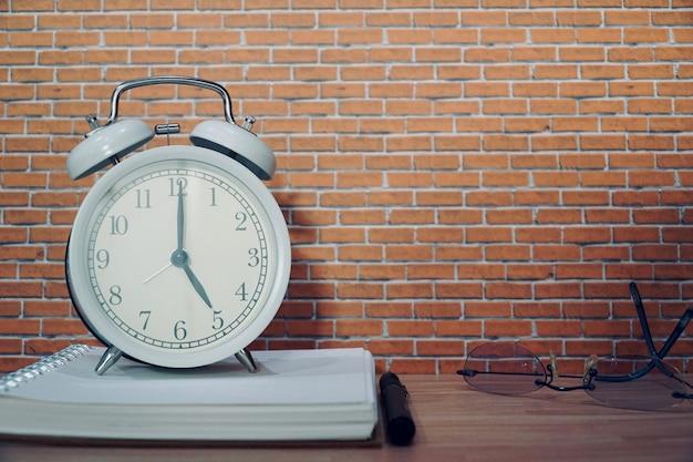 Винтажные белые часы на тетради с стеклами и ручкой. рабочая область в офисе.