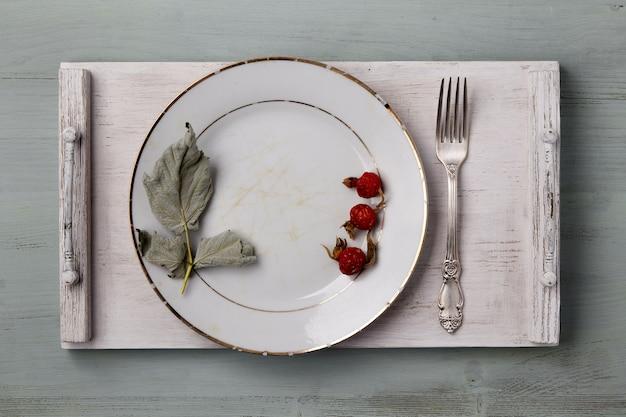 Винтажное белое блюдо, украшенное сушеными листьями и ягодами с вилкой на деревянном подносе на голубом столе. меню верхнего вида
