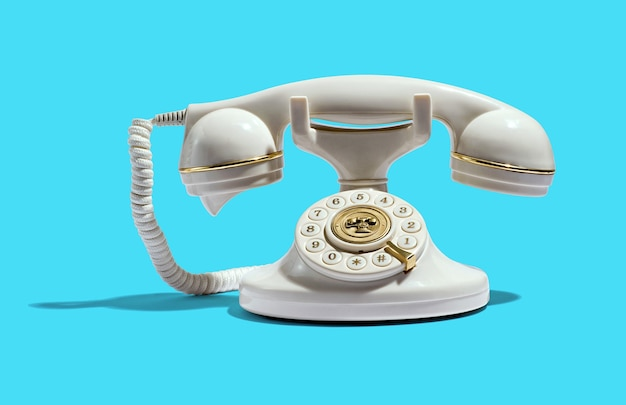 Vintage white telephone with shiny golden ornaments on handset and dial placed on cyan background