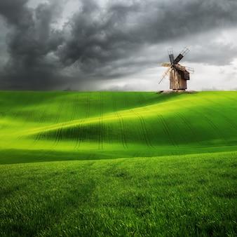 丘の上のヴィンテージ風車、緑の麦畑、農業景観