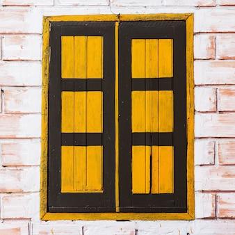 Винтажное окно на желтой цементной стене можно использовать для фона