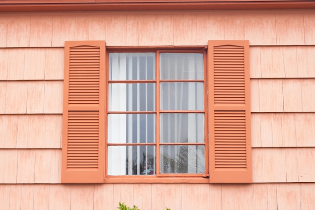 Vintage window with orange tone wall