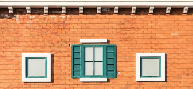 Vintage windows on orange wall in building.