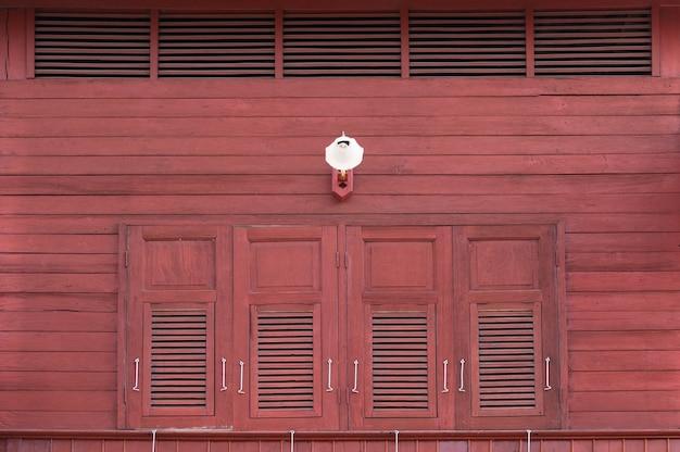 Старинные окна с деревянными ставнями на фасаде и старинные лампы