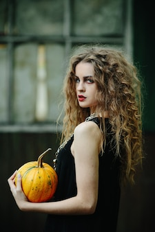 Vintage woman as witch, posing against the backdrop of an abandoned place on the eve of halloween