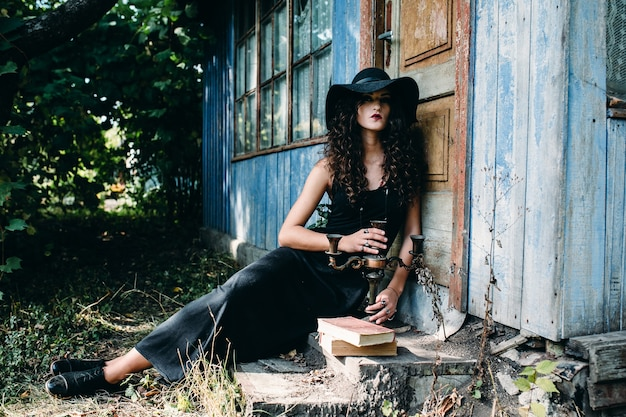 Vintage woman as witch, posing beside an abandoned building on the eve of halloween