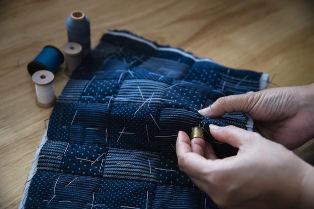 Vintage woman sewing cloth by hand with embroidery set on wooden table - people and handmade diy housework concept
