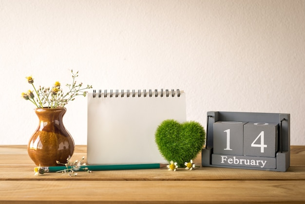 Vintage wood calendar for february 14 with green heart, notebook