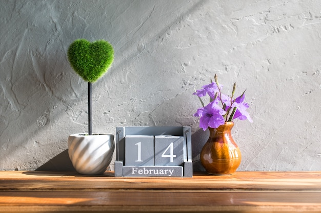 Vintage wood calendar for february 14 with green heart on wood table love and valentine's day concept background, backdrop.