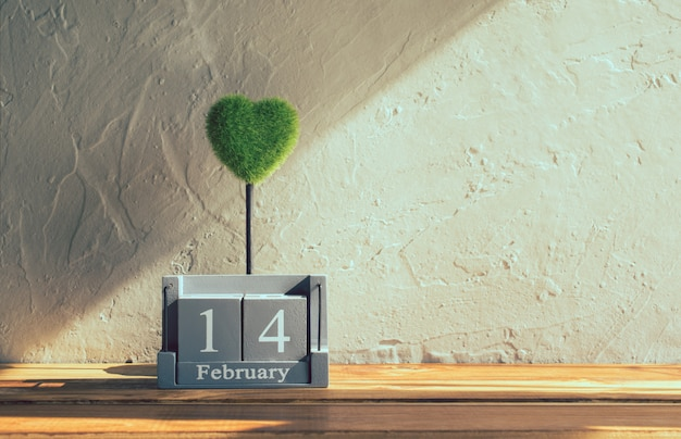 Vintage wood calendar for february 14 with green heart on wood table