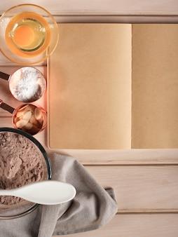 Винтажный деревянный кухонный стол с пустой поваренной книгой, ингредиенты для выпечки торта, яйца, мука, молоко, масло