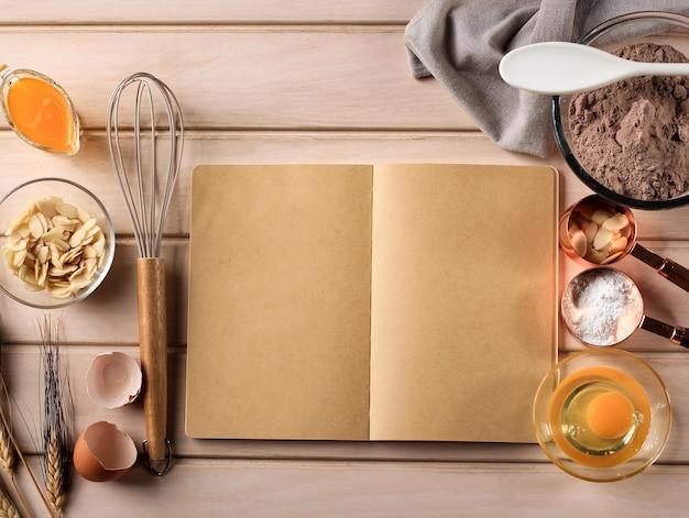 Винтажный деревянный кухонный стол с пустой поваренной книгой, ингредиенты для выпечки торта