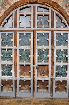 鉄の縁取りと模様入りのガラスを備えたヴィンテージの木製アーチ型ゲート。カザン