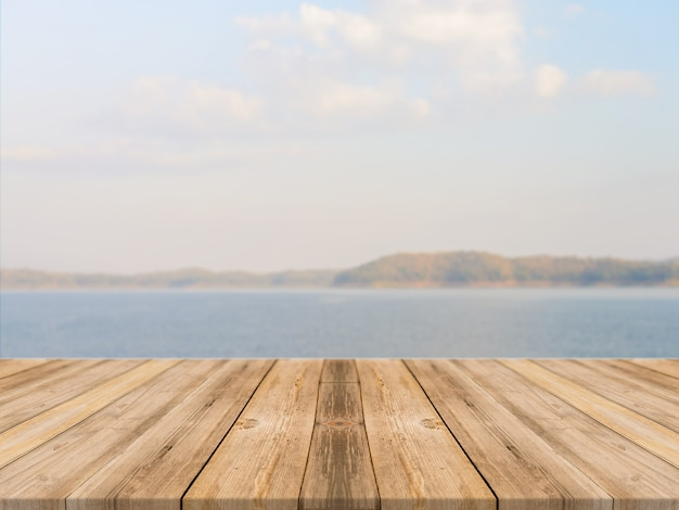 Vintage wooden board empty table in front of blue sea & sky background.
