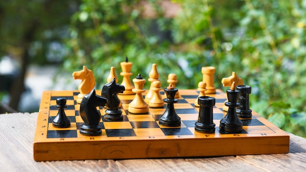 Vintage wooden chess board and figures on table in garden