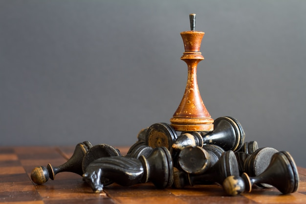 Vintage wooden chess pieces on an old chessboard, selective focus.