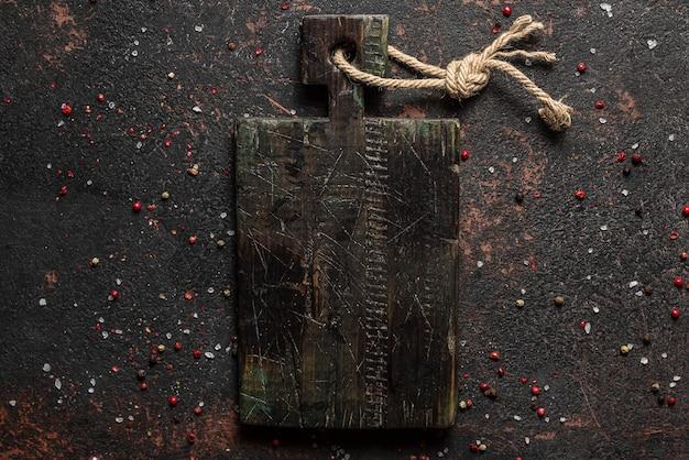 暗いコンクリートの表面で調理するためのヴィンテージの木製まな板とスパイス