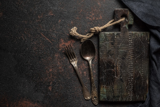 어두운 콘크리트 표면에 빈티지 나무 커팅 보드, 칼 붙이 및 주방 수건