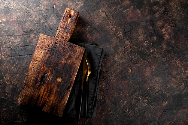 Vintage wooden cutting board linen napkin and cutlery on dark rusty background food background
