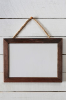 Vintage wooden frame of blank to hang on a wooden wall.