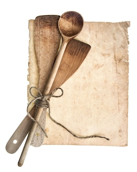 Vintage wooden kitchen utensils and old cookbook page isolated on white background. grandma's recipies concept