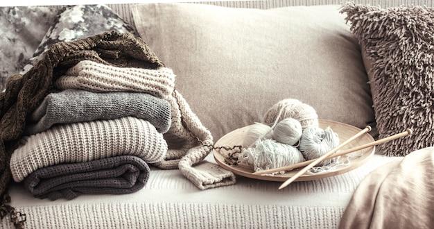 Старинные деревянные вязальные спицы и нитки для вязания на уютном диване с подушками и свитерами