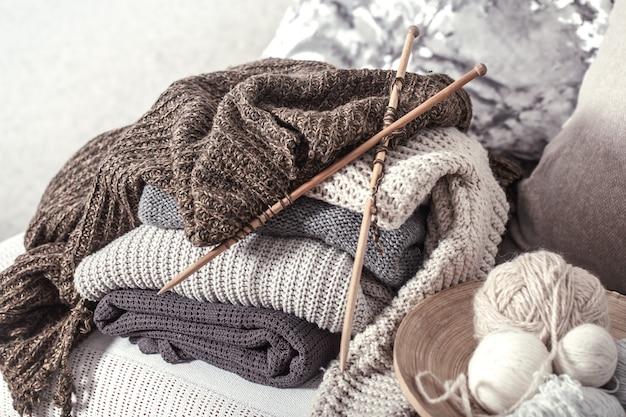 Винтажные деревянные спицы и нитки для вязания на уютном диване с подушками и свитерами