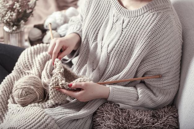 여자의 손에 빈티지 나무 뜨개질 바늘과 실