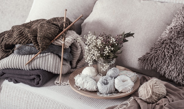 Vintage wooden knitting needles and threads on a cozy sofa with pillows and a vase of flowers