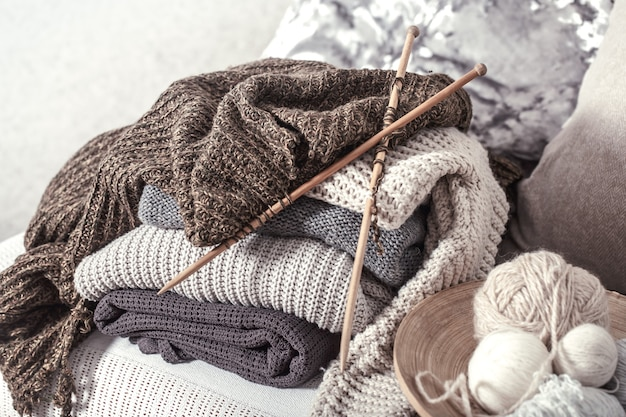 Ferri da maglia in legno vintage e fili per lavorare a maglia su un comodo divano con cuscini e maglioni