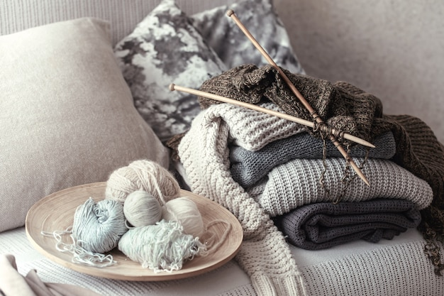 Vintage wooden knitting needles and threads for knitting on a cozy sofa with pillows and sweaters