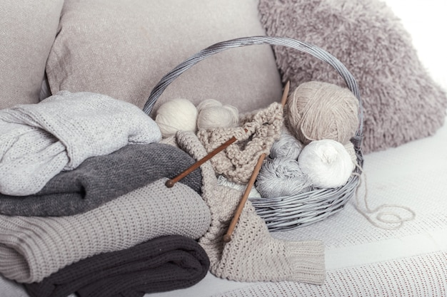Vintage wooden knitting needles and threads in a large basket on a cozy sofa with sweaters. still life photo