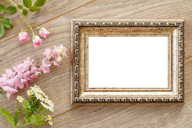 Vintage wooden photo frame with copy space and pink flowers on wooden surface. top view.