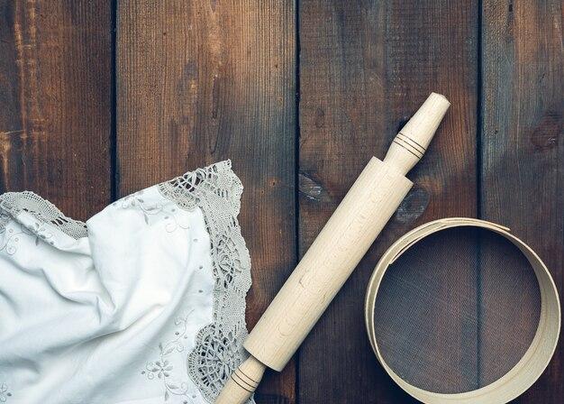 Винтажная деревянная скалка и круглое сито, серая льняная салфетка, вид сверху, кухонная утварь для замешивания теста