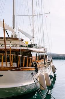 ヴィンテージの木製帆船、ヨットは茶色の漆塗りの木材で海岸デッキに係留されています