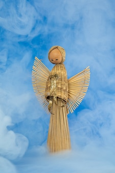 Vintage wooden straw reed angel angel doll against blue background with misty smoke