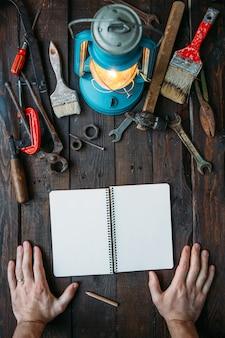 ツールと空のノートブックとフレームに手でビンテージワークベンチトップビュー