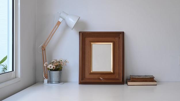 Винтажное рабочее пространство с пустой рамкой, горшечным растением, лампой и старой книгой на белом столе.