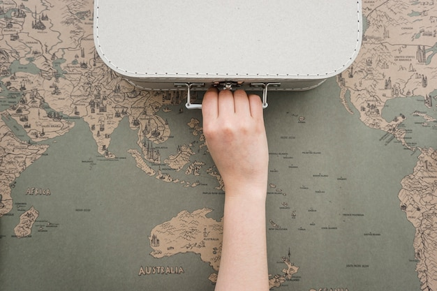 Vintage world map background with hand grabbing a suitcase